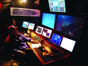 Dr. Robert Ballard watches the bow of the Titanic 6/4 come into view on plasma screens in the control van, as the ROV Hercules photographs the shipreck on HD cameras 12,500 feet below. NOAA oceanographer Catalina Martinez sits to his left. She is part of the ocean exploration program, which supported the expedition by providing the NOAA research vessel Ronald H. Brown.