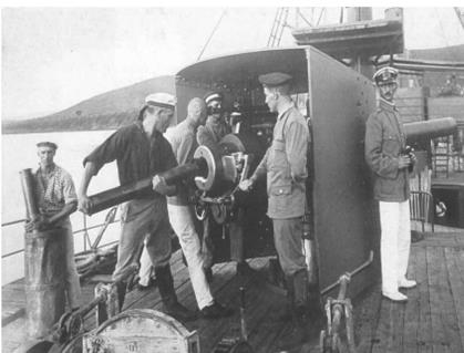 Loading ammunition into guns on the deck of the ship during WWI